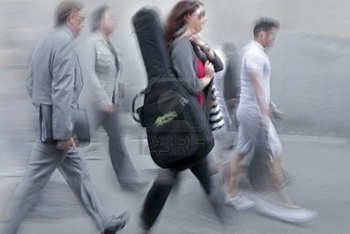 9959827-people-rushing-on-the-street-in-intentional-motion-blur-female-musician-carrying-instrument-
