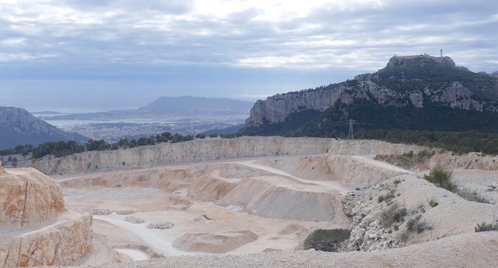 Derrière la carrière, entre le Faron (à gauche) et le Mont Caume (à droite) la rade de Toulon. Au fond le massif du Cap Sicié