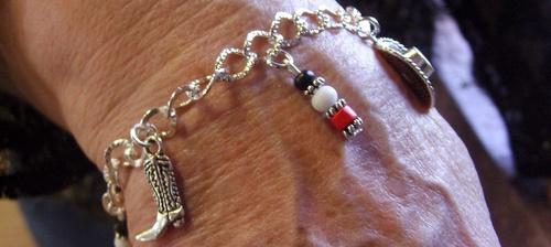 Bracelet country dans les tons rouges, noirs et blancs avec ses breloques santiags, étoiles et chapeau