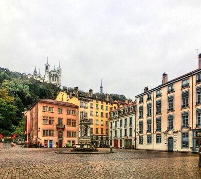 Vue d'une place avec des maisons colorées à trois étages sur deux côtés; au fond, une colline boisée et une basilique.
