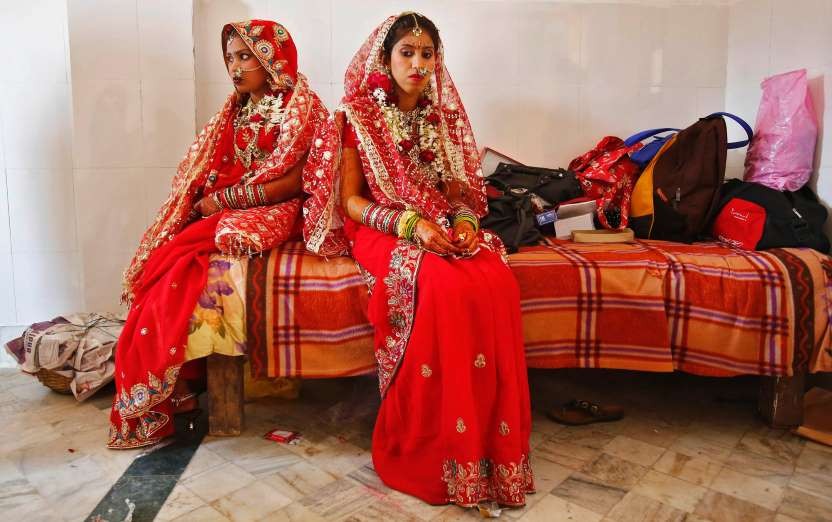 Brides sit after their make-up was done during a mass wedding ceremony at a temple in New Delhi March 3, 3014. A total of 11 couples exchanged wedding vows on Monday during the mass wedding ceremony arranged by a Hindu voluntary organisation, organisers said.