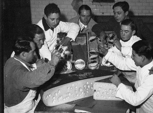 1936, grève dans l'alimentation chez Damoy ; employés jouant aux cartes sur des meules de gruyère