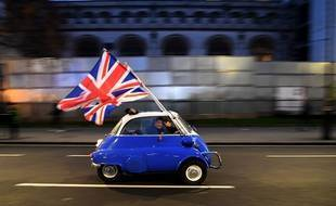 TOPSHOT - A man waves Union flags from a BMW Isetta as he drives past Brexit supporters gathering in Parliament Square, in central London on January 31, 2020, the day that the UK formally leaves the European Union. - Britain on January 31 ends almost half a century of integration with its closest neighbours and leaves the European Union, starting a new -- but still uncertain -- chapter in its long history. (Photo by DANIEL LEAL-OLIVAS / AFP)