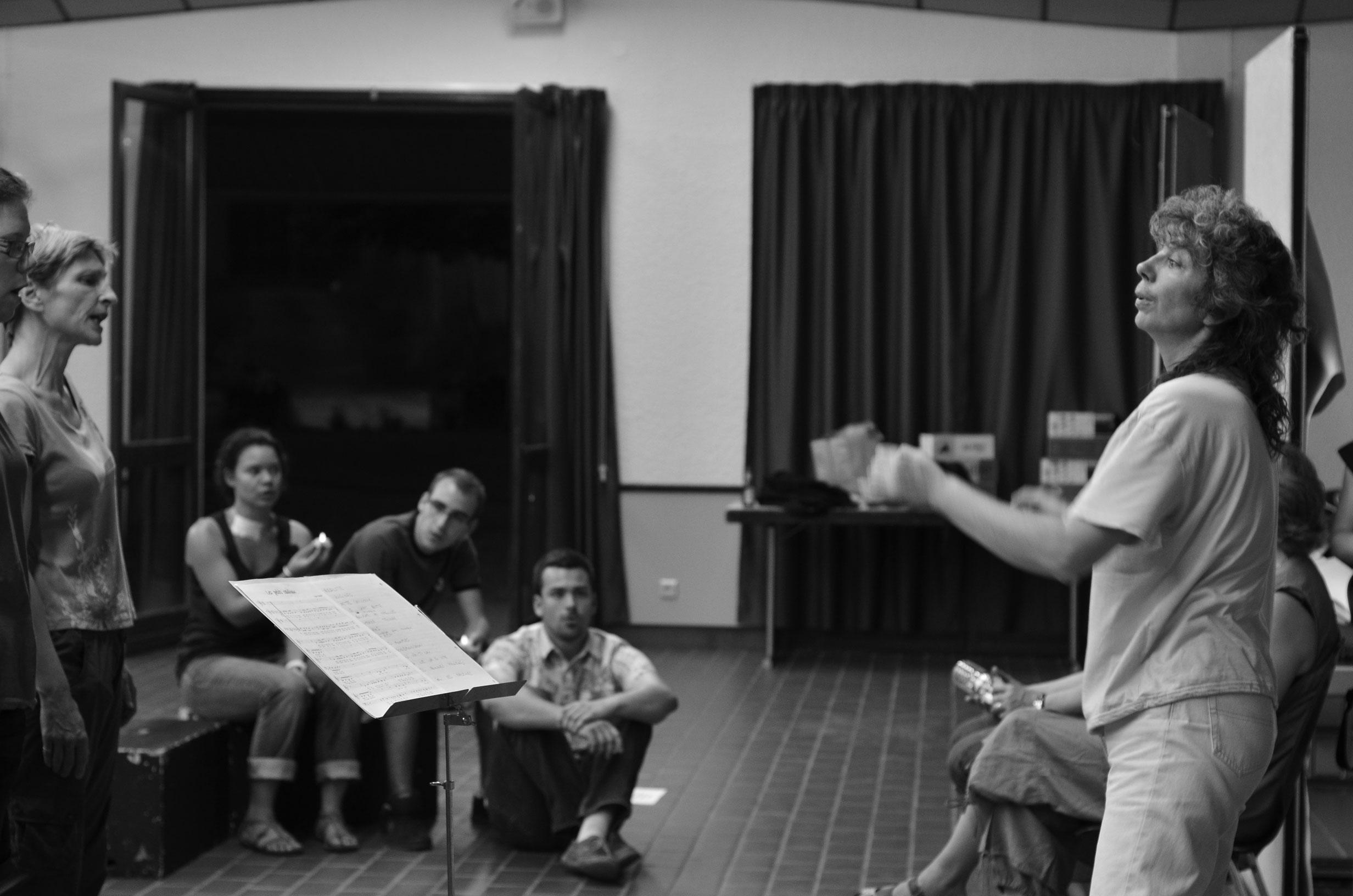 Choristes et chef de choeur en répétition. Photo noir et blanc