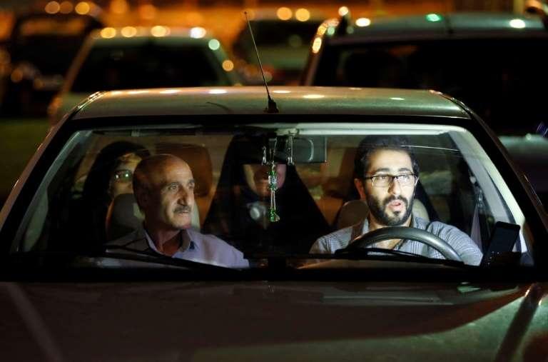 Des Iraniens assistent en famille à une cérémonie religieuse en drive-in sur un parking de Téhéran, le 30 avril 2020