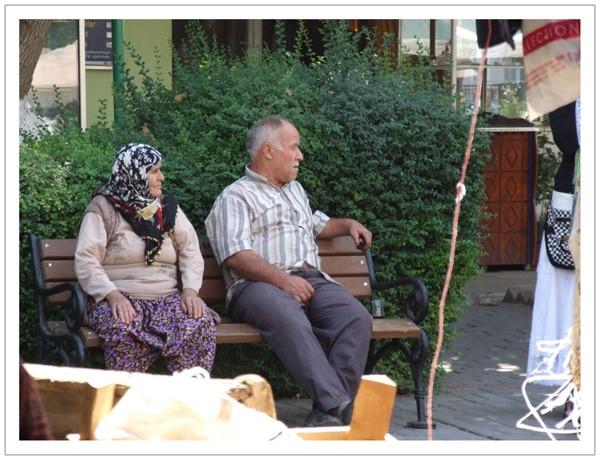 Assis sur un banc, un couple écoute....