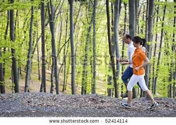 stock-photo-woman-and-man-jogging-on-gravel-path-beside-each-other-with-green-beech-forest-in-backgr
