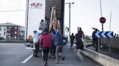 Des migrants profitent du fait qu'un camion à destination de l'Angleterre s'arrête à un stop pour tenter de s'introduire à l'intérieur, le 9 octobre 2014, à Calais.