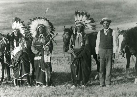 """1890 dans la Dakota du Sud, quatre sioux posent pour le photographe, avec l'un d'eux habillé en """"homme blanc"""" (""""in white man's clothing"""")"""