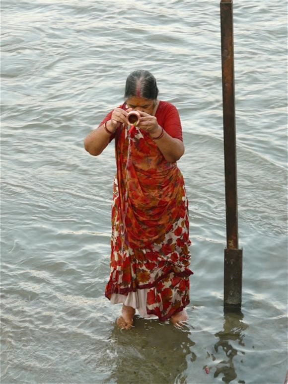 portait de femme en prière dans le Gange
