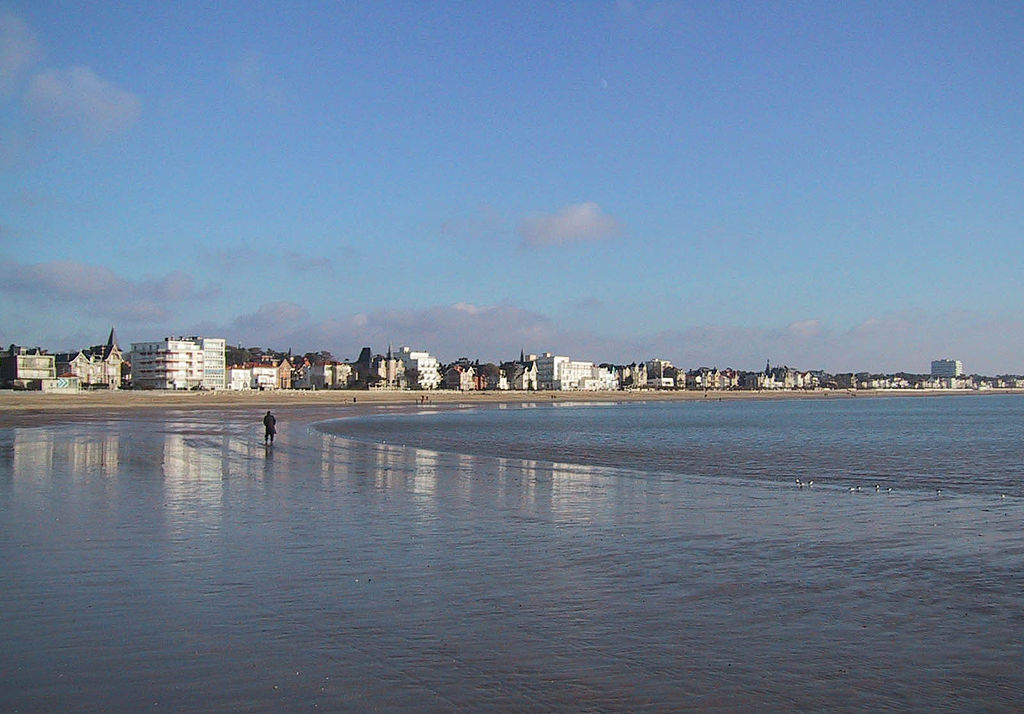 Photographie montrant une grande plage de sable fin de forme courbe à marée basse