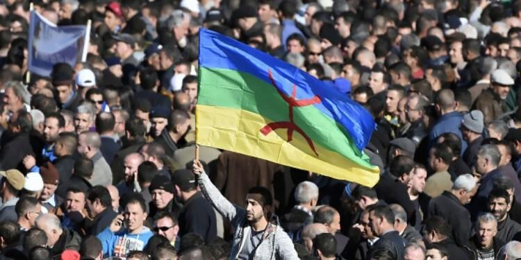 Illustration : Un homme brandit le drapeau amazigh