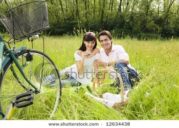 stock-photo-couple-having-a-picnic-in-a-park-smiling-and-looking-at-the-camera-12634438