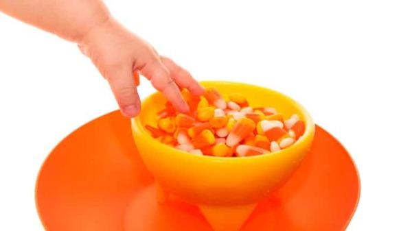 La main de tout-petit sélectionne le maïs bonbon dans un bol d'Halloween jaune