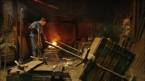 Jean-Claude alimente le four, juste avant de couler le bronze. Dans l'atelier rompu par le temps, qui fermera dans quelques jours, le fondeur parisien répète des gestes séculaires. (Patrick Aventurier/Gamma)