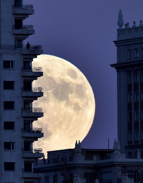 "TOPSHOT - A man stands on a balcony of a building of Madrid as the moon rises in background, on November 13, 2016, on the eve of a ""supermoon"". On November 14, 2016, the moon will orbit closer to the earth than at any time since 1948, named a 'supermoon', it is defined by a Full or New moon coinciding with the moon's closest approach to the Earth. / AFP PHOTO / GERARD JULIEN"
