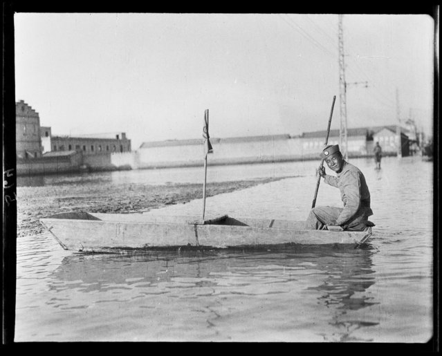 Policeman in boat during a flood. China, Tianjin, 1917-1919. (Photo by Sidney David Gamble)