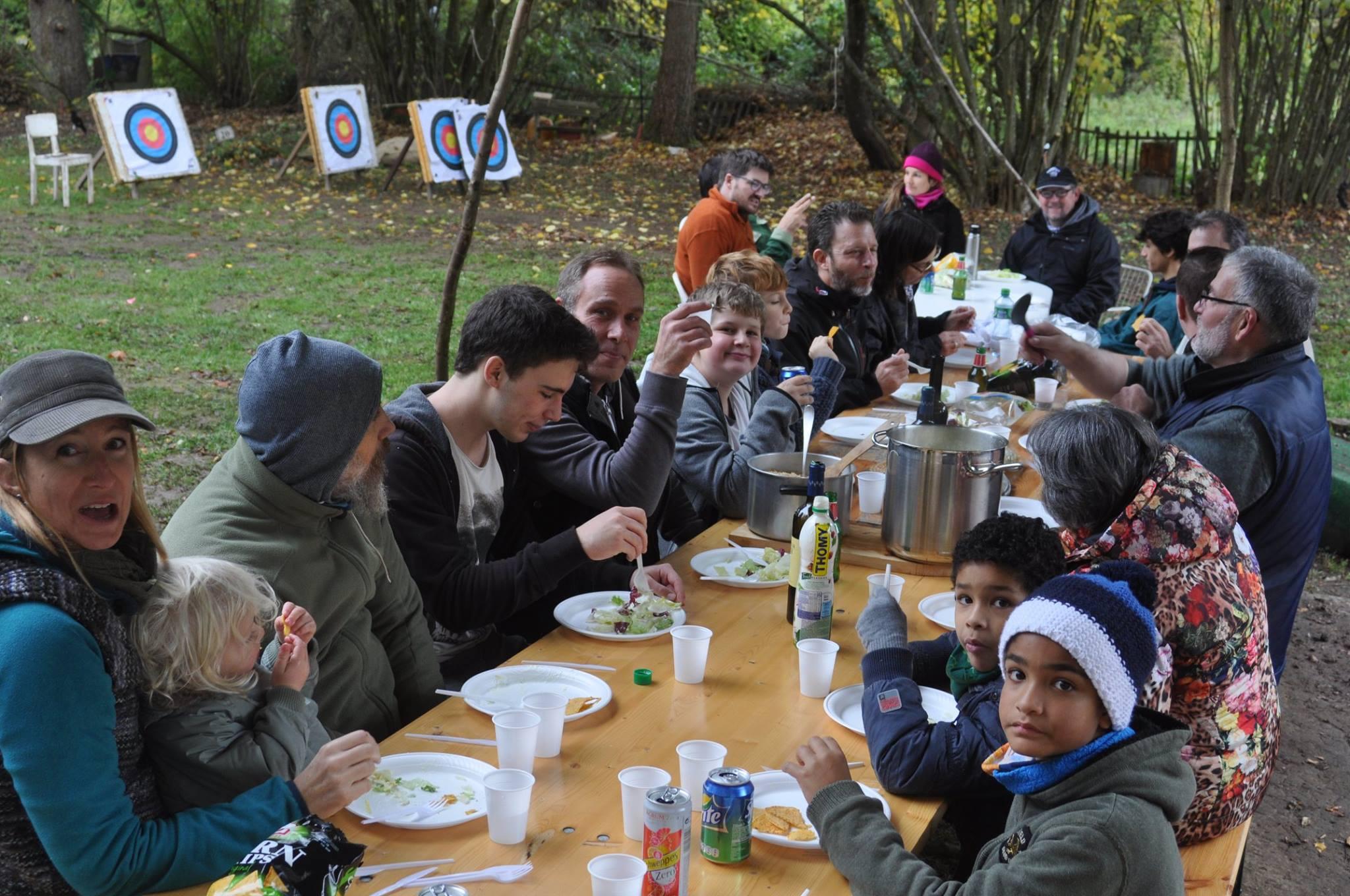 L'image contient peut-être: 8 personnes, personnes souriantes, personnes assises, personnes qui mangent, enfant, table et plein air