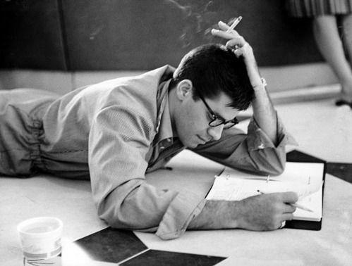 Une photo en noir et blanc de l'acteur Jerry Lewis, couché sur le ventre, en train d'écrire et de fumer une cigarette.
