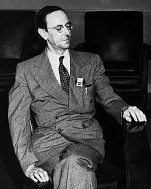 Photo en noir et blanc. Homme aux cheveux foncés portant un veston.