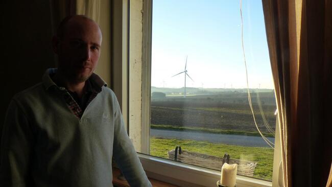 Thibaud Sailly dans sa cuisine avec, en fond, les éoliennes qui jouent avec le soleil.