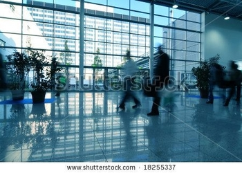 stock-photo--people-moving-in-glass-corridor-18255337