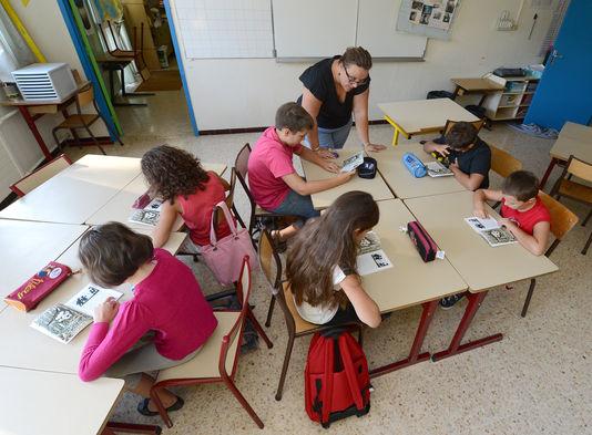Des écoliers effectuent un exercice de lecture, à Vitrolles (Bouches-du-Rhône), en août 2012.