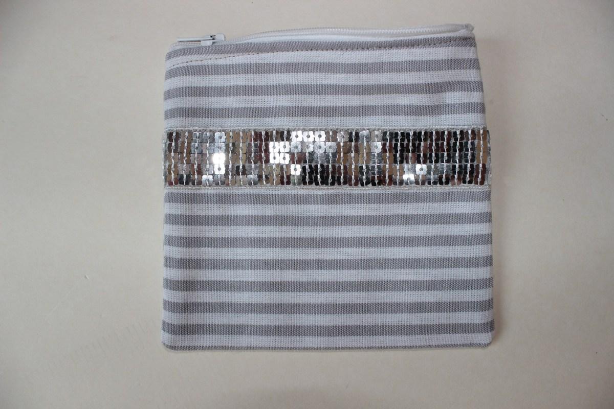 Un sac à paillettes gris et sa trousse