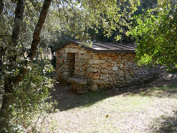 Une cabane reconstruite qui abrite des panneaux didactiques sur l'industrie du charbon de bois