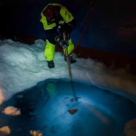 Person står på isen, ved et stort hull som eksponerer vannet under, og opererer et instrument nedi hullet.