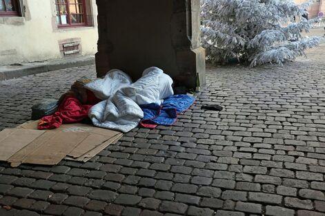 Deux sans-abris dorment sur des cartons en hiver au centre-ville de Colmar.