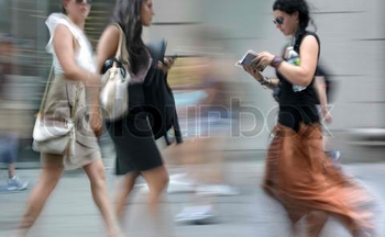 2141427-225696-three-women-walking-on-a-city-street-in-motion-blur-one-of-them-reading-book