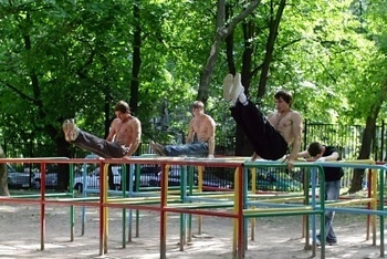 7292187-the-group-of-young-men-doing-exercises-on-playground-equipment-bars-summertime