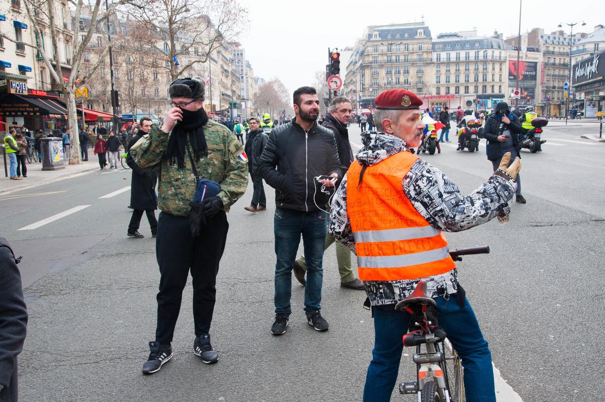 La présence d'antifas dans la manifestation a poussé notre catholique intégriste nationaliste à poser le gilet pendant un temps. Etrangement, il était en discussion avec un manifestant arborant un gilet aux couleurs de l'UPR. - © Reflets