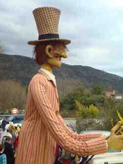 Carnaval de Saillans-Drôme--la grande Marionnette balade sa carcasse rue des Remparts;