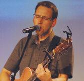 Justin Graves chantant et jouant de la guitare.