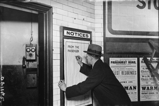 A man writing on a complaints poster on the London Underground, 1922. (Photo by Topical Press Agency/Getty Images)
