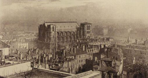 Photographie sépia d'une cathédrale dominant un quartier urbanisé, le tout dans la brume.