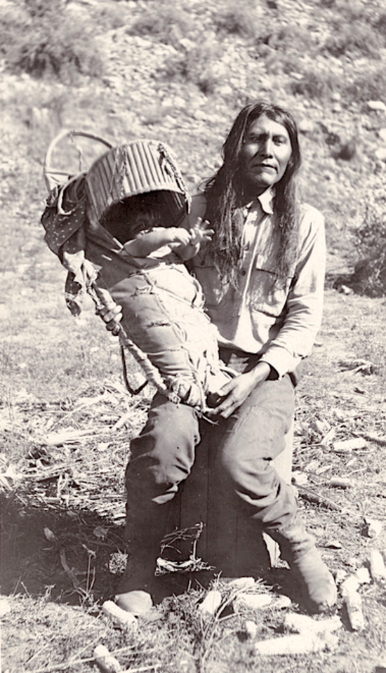 David Ethelbah with a baby. White Mountain Apache. ca. 1919. Arizona. Photo by Edward H. Davis. Sour