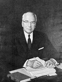 Photo en noir et blanc. Un homme avec cheveux blancs est assis derrière un bureau recouvert de papiers. Portant veston et lunettes, il regarde en direction de l'appareil-photo.