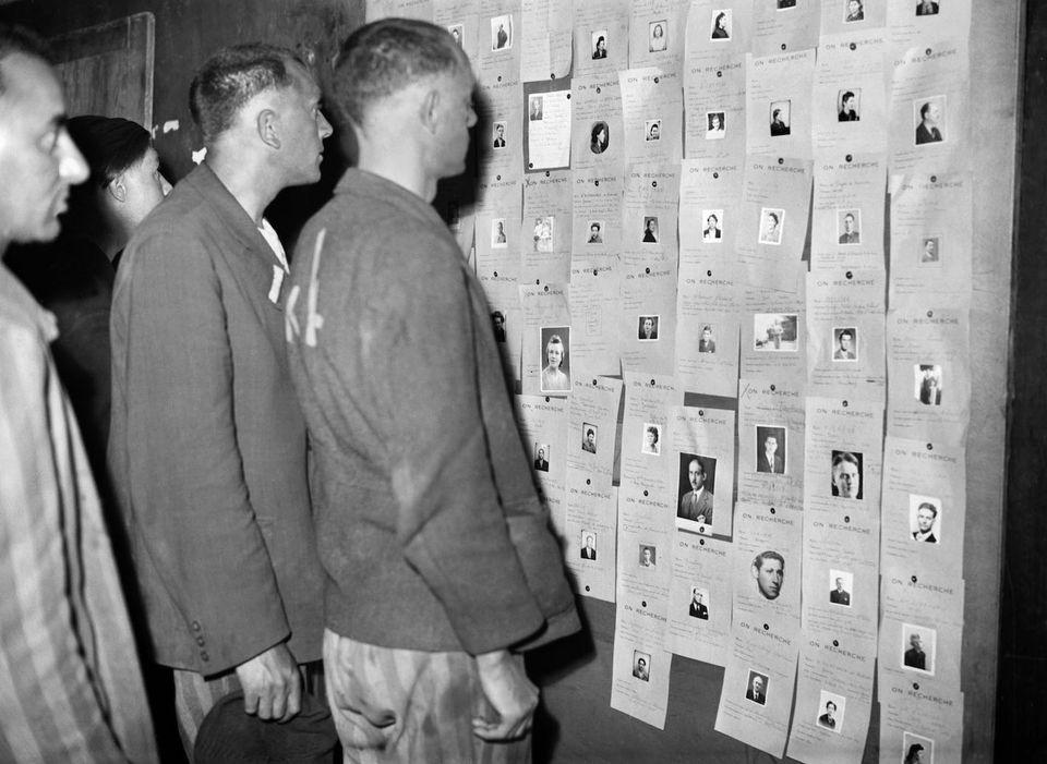 Photo prise en mai 1945 à l'hôtel Lutetia de prisonniers libérés consultant la liste des personnes déportées recherchées après la libération des camps.