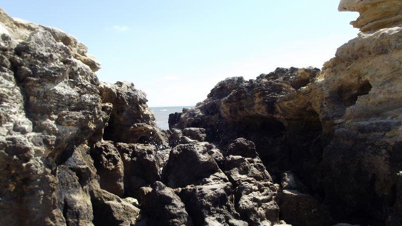 Sur la gauche on aperçoit les deux cabanes de pêcheurs installées en bout de pointe. Quand je passe d'une roche à l'autre je m'engage dans des chaos rocheux où la mer s'engouffre, envoyant des giclées à chaque vague.