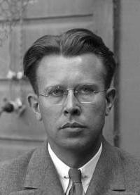 Photo en noir et blanc. Homme portant des lunettes.