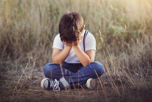 Enfant triste assis par terre, visage caché par ses mains