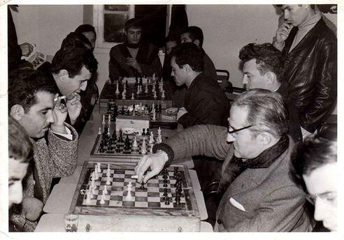 L'image contient peut-être: 4 personnes, personnes assises, échecs et table