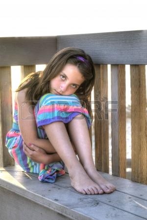 Jolie petite fille avec l'expression solemne assis sur un banc, les bras enroulés autour des jambes et de la tête couchée sur les genoux à la plage Banque d'images - 19226424