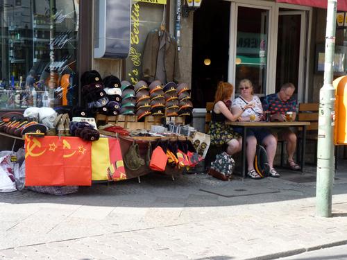 Etal de casquelttes d'uniformes et terrasse de café vers check point Charly