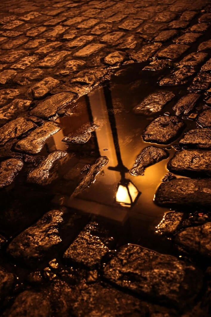 Reflet d'un lampadaire dans une rue pavée