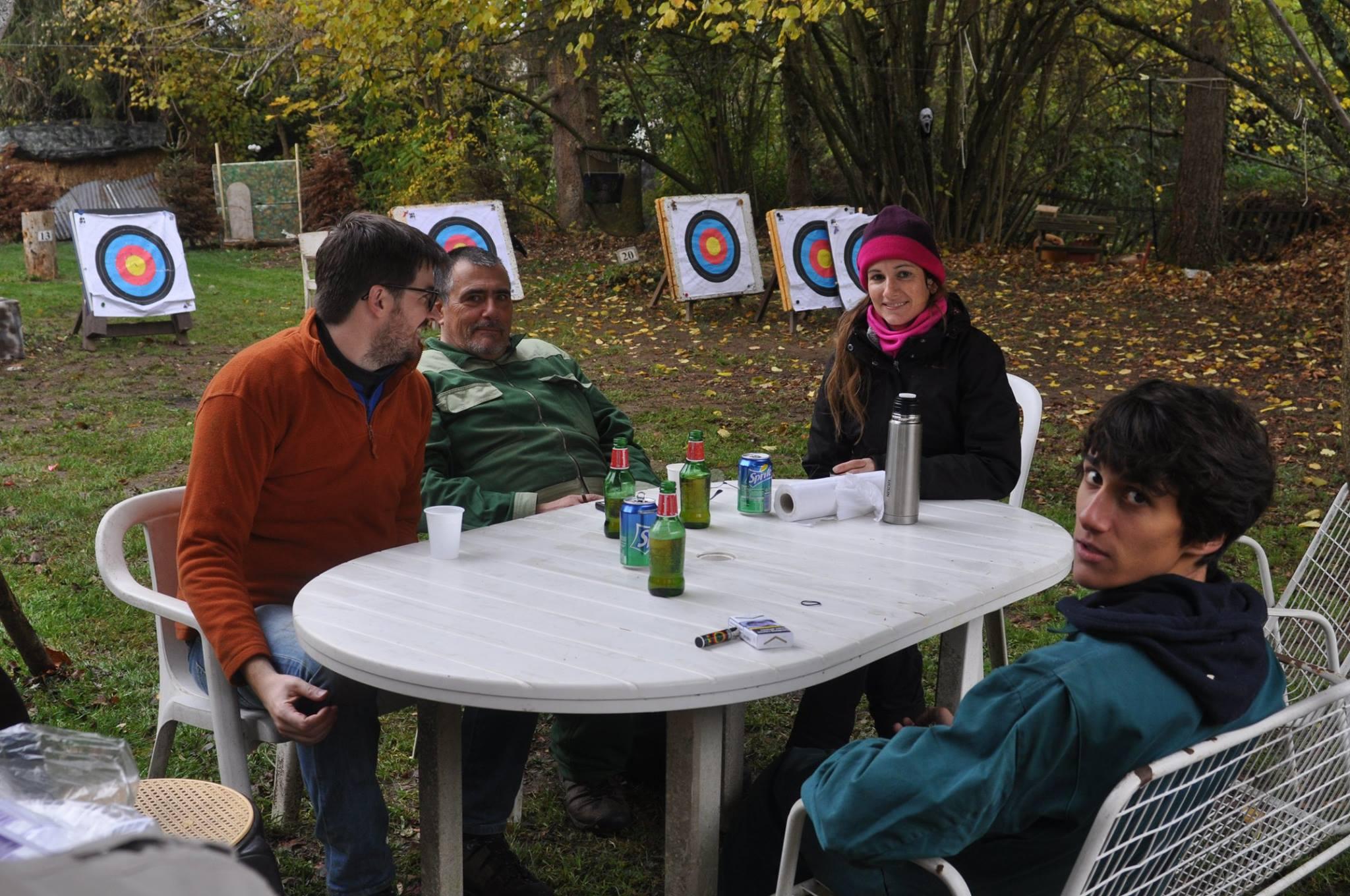 L'image contient peut-être: 3 personnes, personnes souriantes, personnes assises, table, chapeau, arbre et plein air