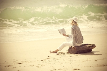 woman-with-hat-reading-book-on-the-beach